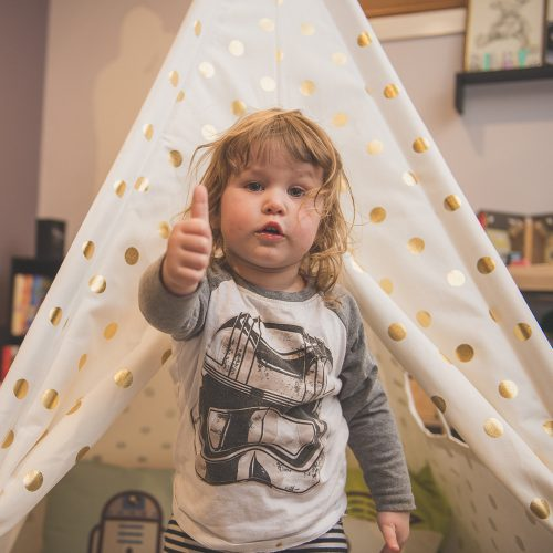 Toddler gives a thumbs up in front of the white gold coin teepee play tent