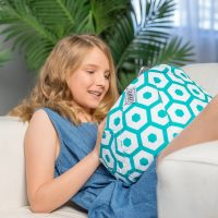 A teenager watches a mobile device, tablet or ipad whilst seated with a bean filled bean bag or cushion on her lap. The bean caddy is white with a green geometric print.