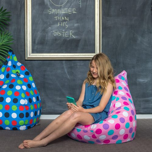 A girl sits on a tear drop shaped kids bean bag that is pink with spots looking at her mobile phone, with a blue kids bean bag, also spotty, nearby.