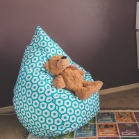 Teddy rests on a mint geo print kids bean bag