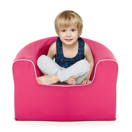 Toddler sits crosslegged in the rasberry pink, solid foam, pop armchair for kids