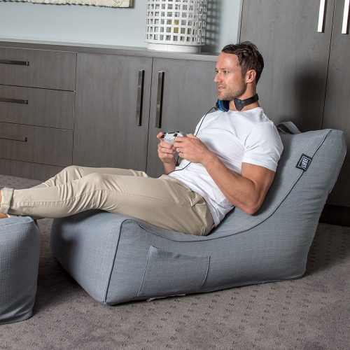 Man with game console sitting on a grey linen beanbag shaped like a lounge with his feet up. A storage pocked it visible.