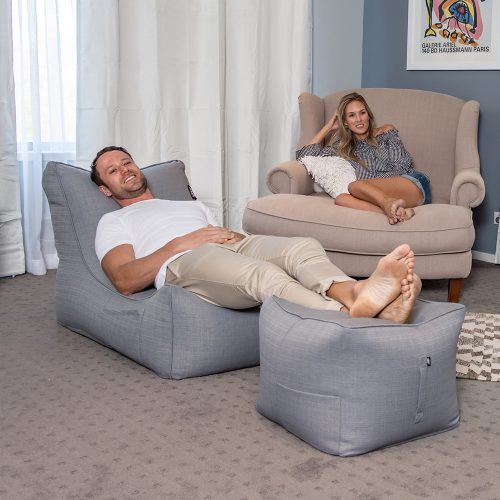 Man fully reclined on a grey linen beanbag shaped like a lounge with his feet up on a matching linen bean bag ottoman. A storage pocked it visible on both pieces of furniture.