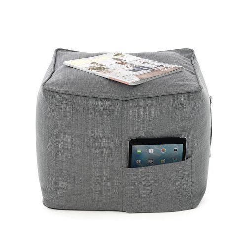 A square grey linen bean bag ottoman that can be use.d as a chair, table or footrest. A magazine rests on top and a iPad or tablet is in the storage pocket