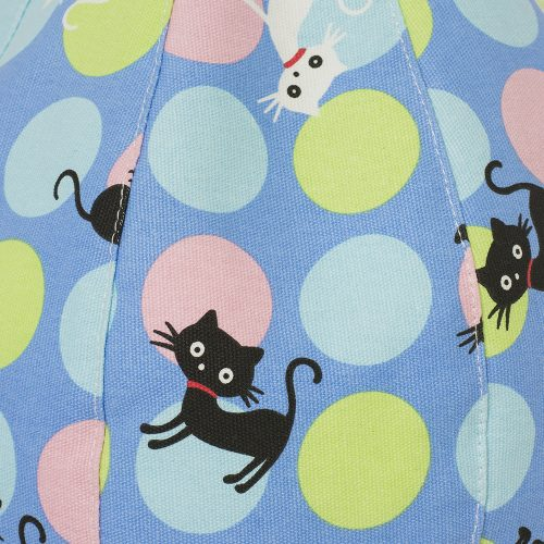 A close up of the texture and color of the pale blue fabric with pastel spots in yellow, blue and pink sprinkled by black and white cats