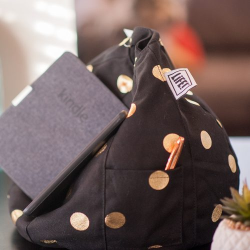 A kindle rests on a bean filled bean bag or bean caddy. A pen sits in the storage pocket and the LiFE! tag is visible. The bean caddy is black with gold spots.