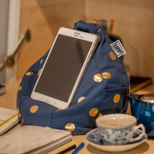 A tablet sits on a navy blue bean filled bean caddy with gold coin spots. A cup or tea, teapot and journal are visible.
