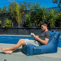 A man reads by the pool in the sunshine sitting on a blue louge shaped bean bag or foam filled pop lounge with white trim. A handle and storage pocket are visible.