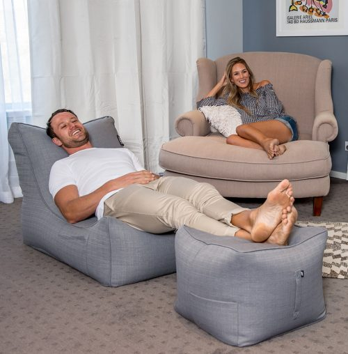 A man smiles and reclines on a lounge shaped grey linen bean bag with his feet resting on a matching grey linen bean filled ottoman.