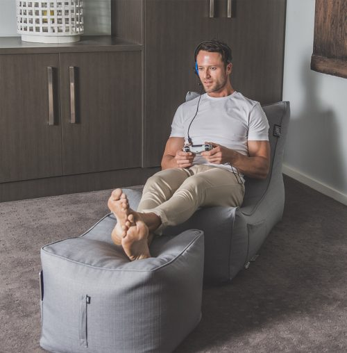 A man is gaming intently with a controller and headset whilst seated in a grey linen bean filled lounge shaped beanbag and cube ottoman. A handle and storage pocket are visible.
