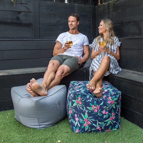 A couple sit enjoying a wine together with their feet up on square bean filled bean bag ottomans. One is grey linen and the other a tropical hibiscus print on a navy background.