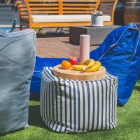 Fruit and a wooden board sit on a blue and white striped bean filled bean bag ottoman. Two bean bag lounge seats in grey and navy blue are along side it.