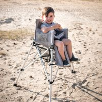 Toddler smiles happily from a portable camp high chair a sandy beach.