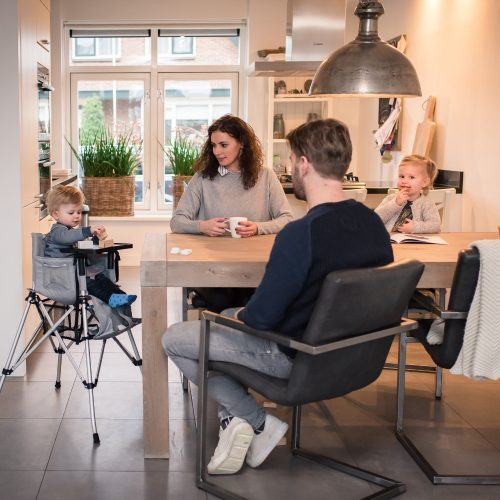 Family sitting around kitchen bench with toddler in a portable travel camp high chair in silver grey