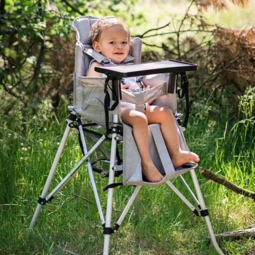 A toddler sits in a silver grey portable camp high chair.