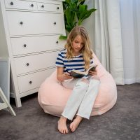 A teenager reads a book curled in a teardrop shaped pink peach velvet bean bag.