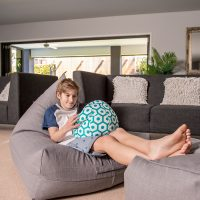 Teenager sits comfortably on a large grey linen luna shaped bean bag with his feet up on a matching ottoman. He is watching a portable device or ipad resting on a small bean bag or bean caddy with a grean and white geometric print.