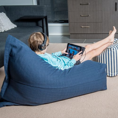 Teenager sits on a navy blue linen beanbag whilst gamin on a portable device wearing headphones. His feet rest on a blue and white striped bean bag ottoman.