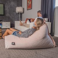Women relaxes on a peach pink velvet luna beanbag. The LiFE brand tag is visible.