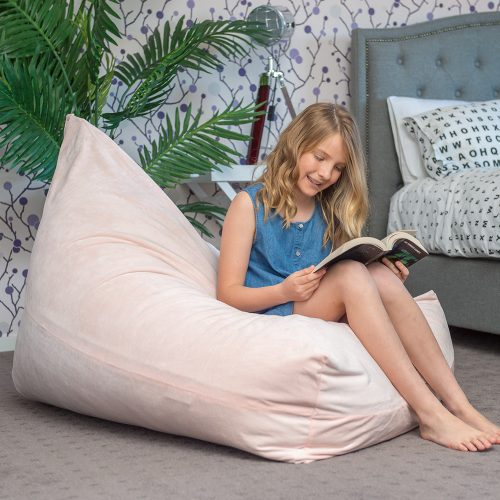 Teenager reading a book seated on a peach pink velvet luna bean bag.