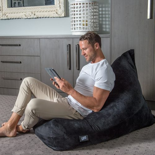 Man sits on a dark slate velvet luna shaped bean bag engrossed in his portable device.