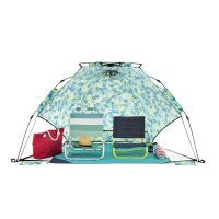 Tropical print adventure shelter from the front with a picnic blanket and two camp chairs fitting easily inside