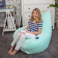 A teen sits on a teardrop shaped bean bag made from mint green velvet.