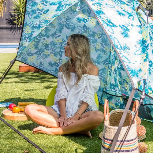 A woman is shaded by the Auto Ezee arlie sun shelter. It has a tropical leaf print in blues and greens.