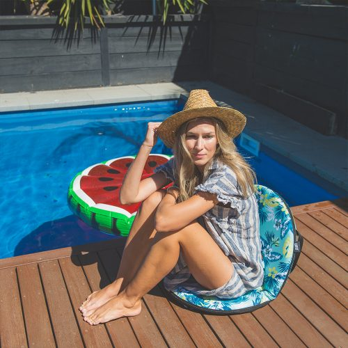 A woman sits poolside holding her sunhat, on a leaf print padded portable cushion recliner seat. The chair has an attractive tropical print in teal, blue, green yellow and white.