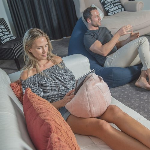 A couple are seated in the lounge. She works from an iPad or tablet resting on a blush peach pink faux fur iCrib bean bag sitting on her lap and he chats whilst seated on a navy blue linen luna shaped bean bag.