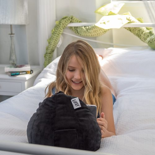 A teenager lays on a bed watching a portable device, mobile phone, tablet or icrib on a small bean bag or cushion. The bean caddy is made from a slate colored velvet.