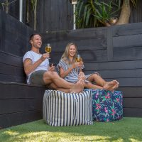 A couple smile over glasses of wine with their feet upon cube shaped, bean filled ottomans. The ottoman beanbags are blue and white striped and a pink tropical print on a navy base color