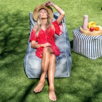 A woman soaks in the sunshine seated on a grey lounge shaped bean bag filled with bean bags or pop foam. She is located on grass in dappled shade with a blue and white striped bean bag ottoman holding fruit nearby.