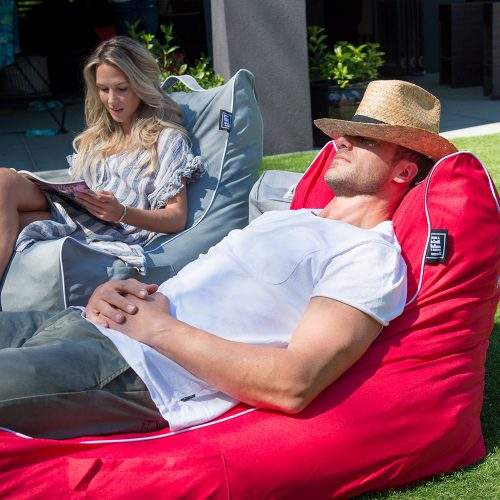A man dozes with his sun hat over his eyes in a red lounge shaped bean bag filled with beans or pop foam. A woman reads a magazine in a grey lounge shaped bean bag nearby.