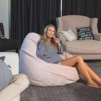 Women sits comfortably on a peach pink faux fur super size bean bag in a traditional tear drop shape.