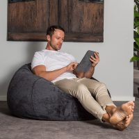 A man reclines in a super size, faux fur, slate colored bean bag whilst using his portable device, table or iPad