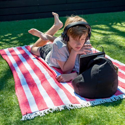 A teenager relaxes on a red and white striped beach towel with headphones on watching an ipad or tablet. The mobile device rests on a black bean filled bean bag so he doesn't have to hold it.