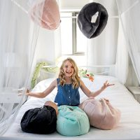 Teen 'juggles' iCribs sitting on a bed in a brightly lit bedroom