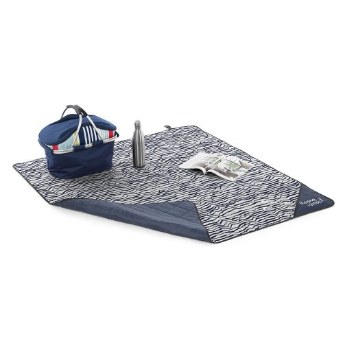 The blue and white wave print marine beach blanket all set up for a picnic with basket, drink bottle and magazine.