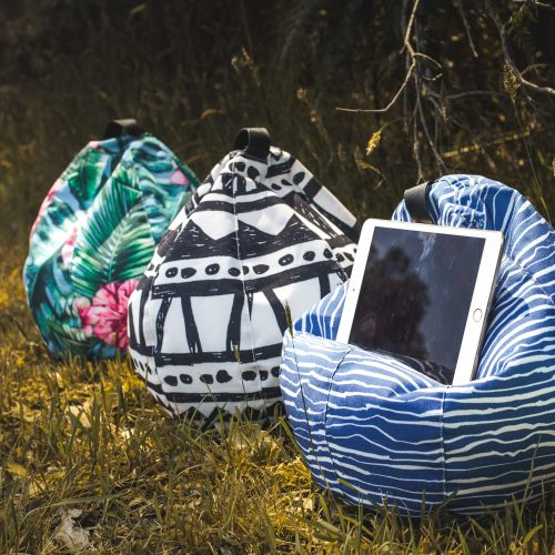 Three icrib bean caddy, book holder, tablet cushion, ipad pillows sit on grass. Wellen, Bermuda and Belvedere designer hand drawn fabrics