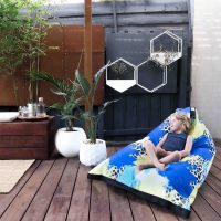 Small boy reclines in the lifestyle tetrahedral shaped bean bag in blue, yellow, green and white Tier material with black contrast trim