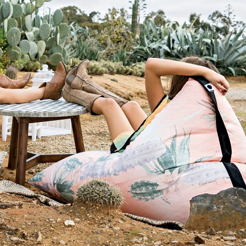 Woman reclines with her feet up on a mosiac table in the lifestyle tetrahedral shaped bean bag in pink and green cactus print Kakteen material with black contrast trim. There are cactus in the foreground and background.