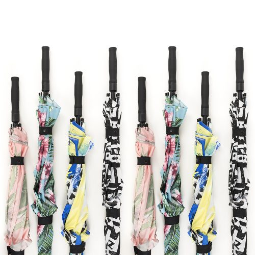 A line of 8 umbrellas in four prints with handles at varying heights