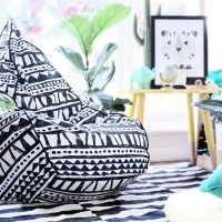 Tear drop shaped bean bag in bold geometric hand drawn designer bermuda fabric in a home with rung, pot plant and side table.