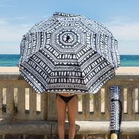 A woman holds the black and white geometric print bermuda sun umbrella leaning against a low concrete wall with a beach in the background