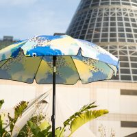 The Tier sun umbrella with black trim on a sunny day with plants and the melbourne shot tower in the background