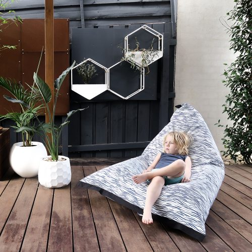 Small child reclines in the lifestyle bean bag in marine blue and white print fabric