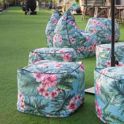 Hand drawn designer tropical print belvedere casual outdoor furniture. Three tear drop bean bags and 4 ottomans are visible on the lawn.