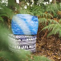 Black and white bermuda print ottoman stacked under a blue and white wave print Wellen ottoman in ferns