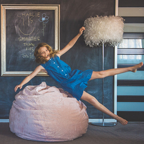 Teen jumps onto a pink velvet teardrop supersize bean bag